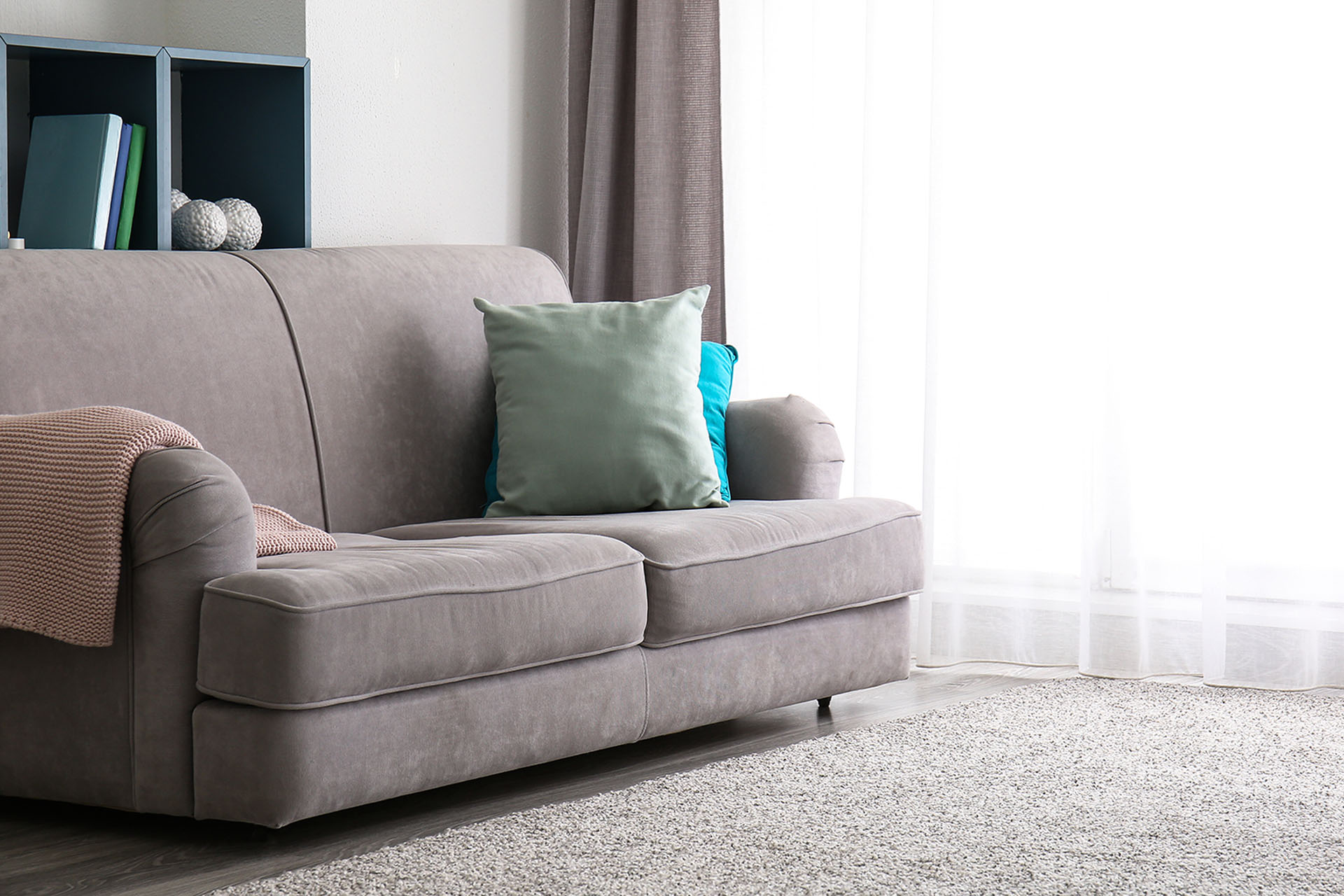 Grey fabric lounge with green cushion